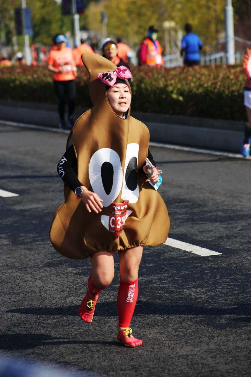 A woman dressed in a novelty costume takes part in the 2020 Shanghai International Marathon, the only Platinum Label road race in the world to take place this year, Shanghai, Nov. 29, 2020. People Visual