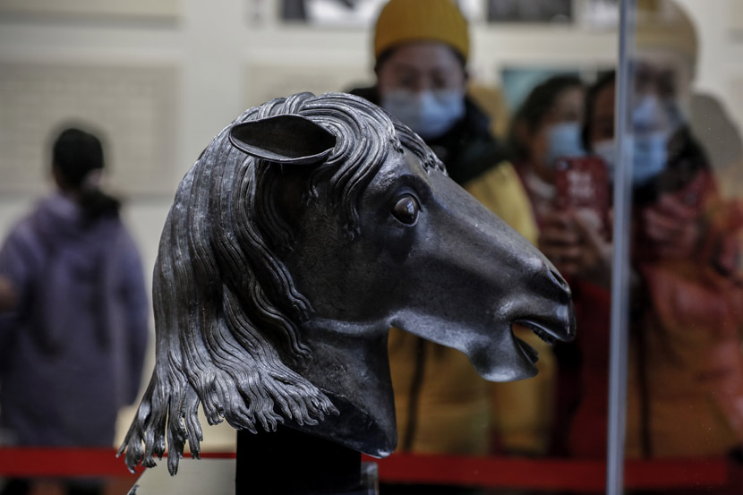 Visitors take photos of a returned bronze horse head sculpture that had been looted 160 years ago by invading Anglo-French forces at the Old Summer Palace, in Beijing, Dec. 3, 2020. People Visual