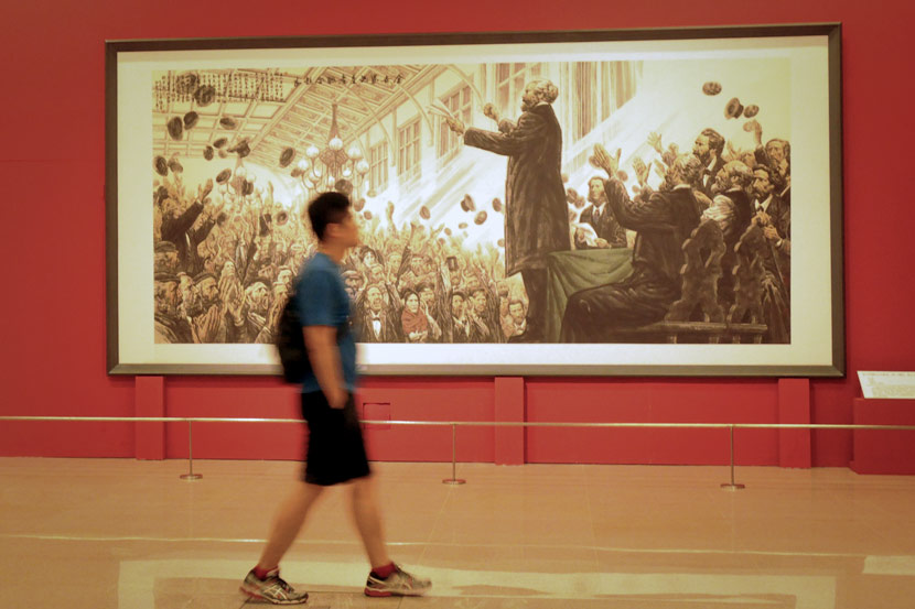 A man walks past an oil painting of Karl Marx during an exhibition in Beijing, May 6, 2018. Du Jia/People Visual