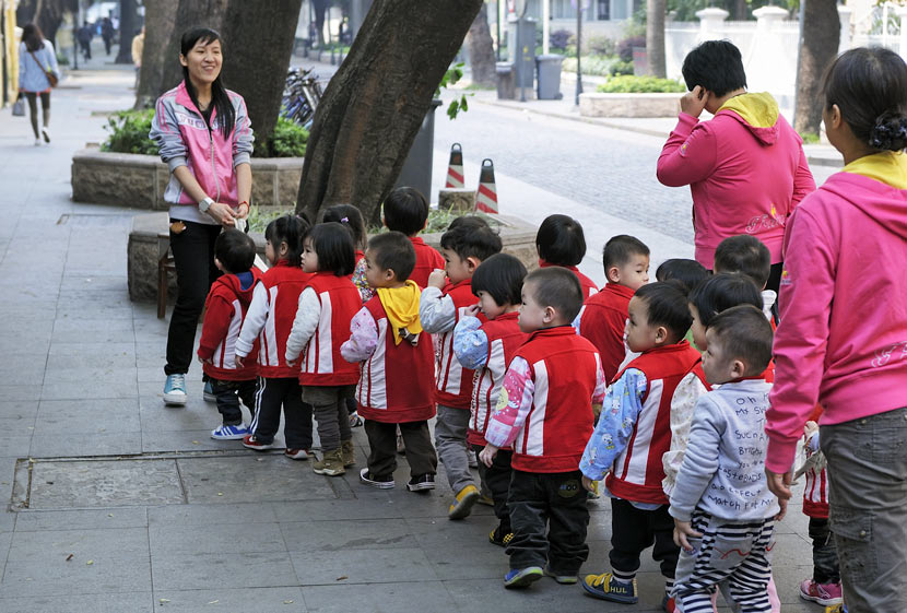 A kindergarten teacher (left) guides her students down a street in Guangzhou, Guangdong province, 2012. People Visua
