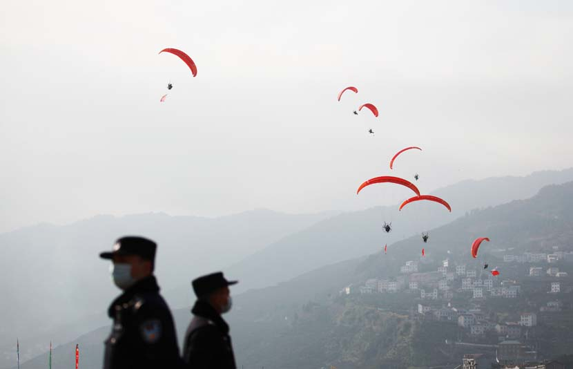 Police officers stand guard during a paragliding show in Yichang, Hubei province, Dec. 12, 2020. People Visual