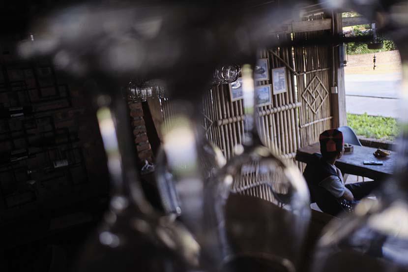Huang Zhicheng sits in his empty bar in Hebian Village, Yunnan province, Nov. 1, 2020. Wu Huiyuan/Sixth Tone