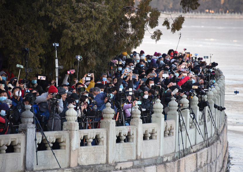 Visitors strain to take photos of Seventeen-Arch Bridge in the Summer Palace, Beijing, Dec. 20, 2020. People Visual