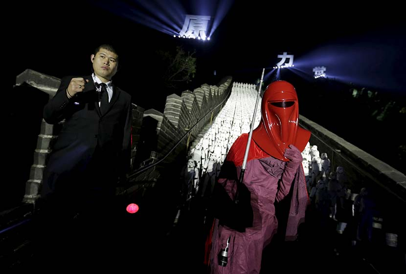 "A person dressed as a ""Star Wars"" character poses for a photo in front of 500 replica Stormtroopers set up at the Great Wall for an event promoting the release of ""Star Wars: The Force Awakens"" in Beijing, Oct. 20, 2015. Li Jiangsong/People Visual"