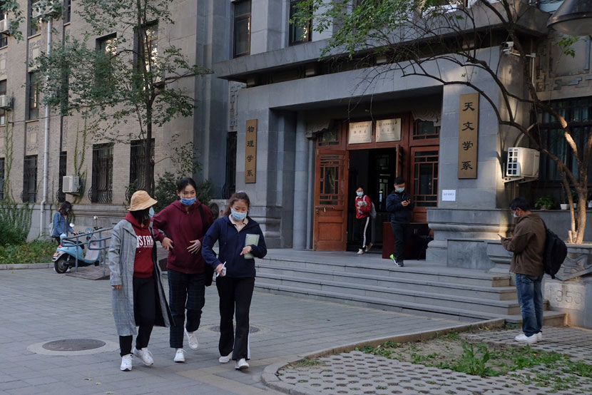 Students walk past the astronomy department building at Beijing Normal University, Oct. 13, 2020. Ye Ruolin/Sixth Tone