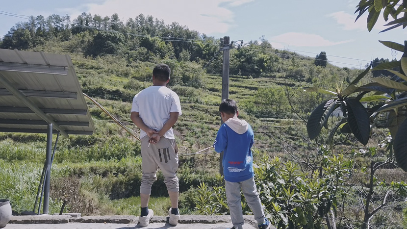 Wang Xiaoping and his son stand outside their mountainside house, in Chongqing, September 2020. He Kai for Sixth Tone