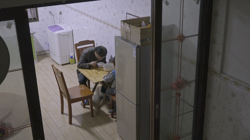 Long Daibing and his youngest son have dinner at their house in rural Chongqing, September 2020. Long gave up his job in Shanghai so he could care for his family. Liu Jingwen for Sixth Tone