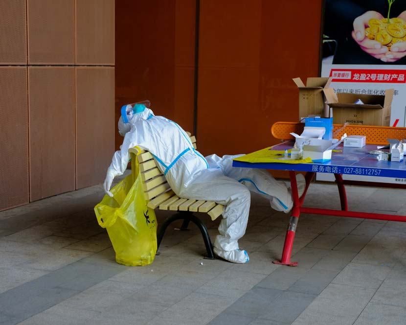 An exhausted medical worker takes a break after giving nucleic acid tests to hundreds of people returning back to work at Wuhan Optical Valley, Hubei province, April 13, 2020. Shi Yangkun/Sixth Tone