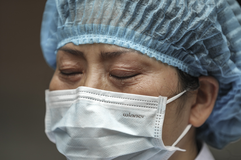 A medical worker cries at a hospital in Wuhan, Hubei province, Feb. 13, 2020. Chen Zhuo/Changjiang Daily/People Visual