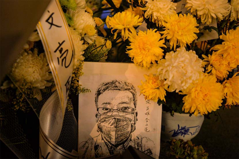 "A portrait of Li Wenliang is placed among flowers sent by residents paying their respects to the doctor at the West Lake section of Wuhan Central Hospital, Hubei province, Feb. 7, 2020. Li Wenliang, an ophthalmologist believed to be one of eight people reprimanded by police in early January for ""spreading rumors"" about a new SARS-like virus, died early Friday morning at the age of 34. Shi Yi for Sixth Tone"