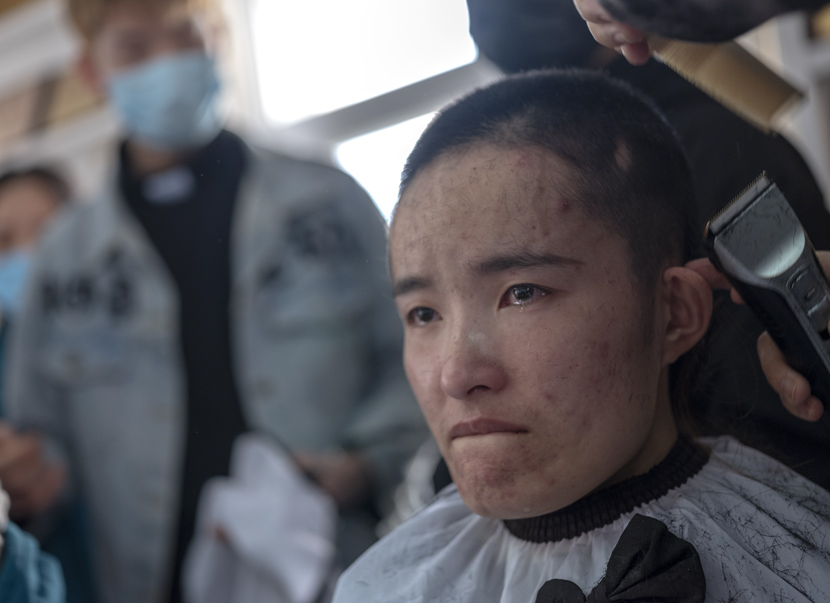 A nurse gets her hair shaved before being dispatched to the front lines of the coronavirus epidemic in Wuhan for medical support, in Sanmenxia, Henan province, Feb. 15, 2020. Du Jie via Xinhua