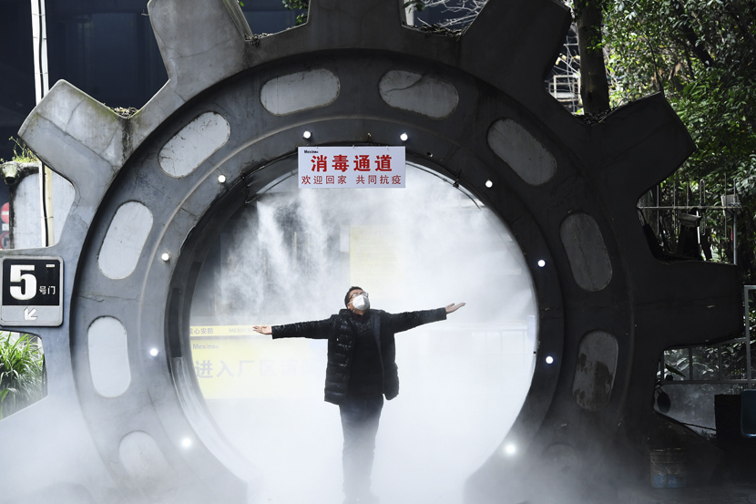A staff member gets disinfected at the entrance of his company in Chongqing, Feb. 10, 2020. Chen Chao/CNS/People Visual