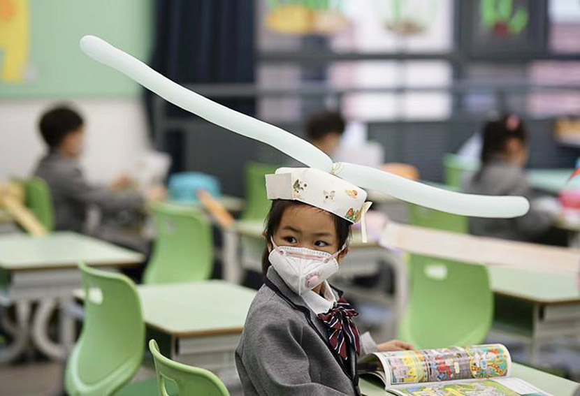 "A girl wears a social-distancing ""one-meter-hat"" during the first day back at a primary school in Hangzhou, Zhejiang province, April 2020. Zhejiang Daily"
