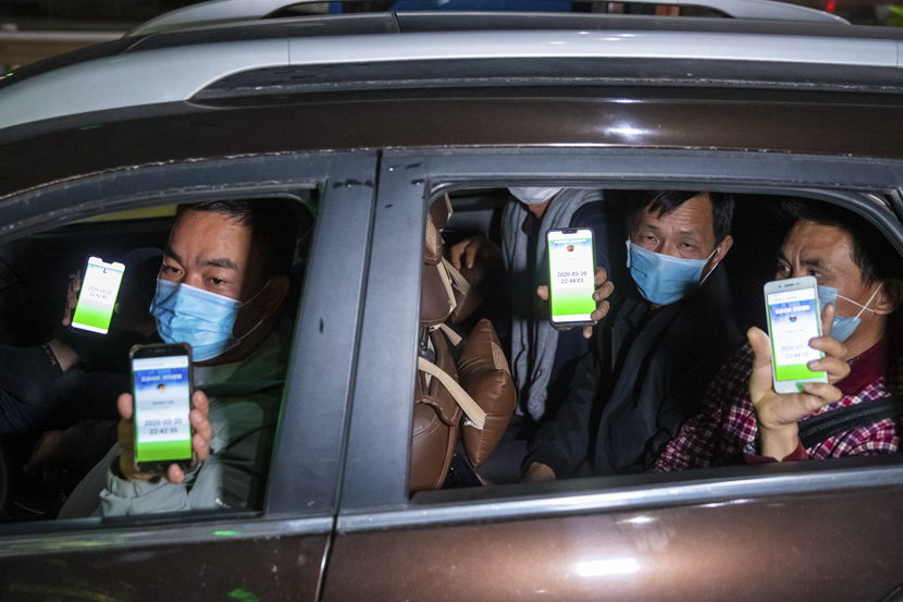 People show their green health codes while passing a quarantine station in Huizhou, Guangdong province, March 20, 2020. Huang Yanhui/People Visual