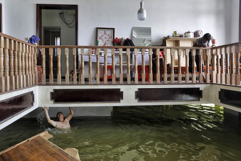 A villager cleans the ceiling of a flooded ground floor in Youdunjie Town, Jiangxi province, July 7, 2020. Li Zhanjun/Southern Metropolis Daily