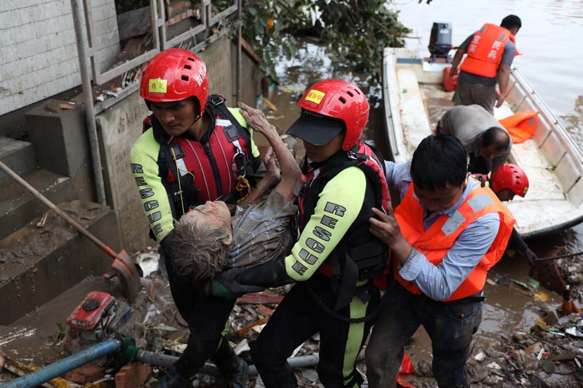 Rescuers transfer an elderly woman to a safe place after floodwaters destroy her house in Yibin, Sichuan province, Aug. 19, 2020. Wang Yushuai/People Visual