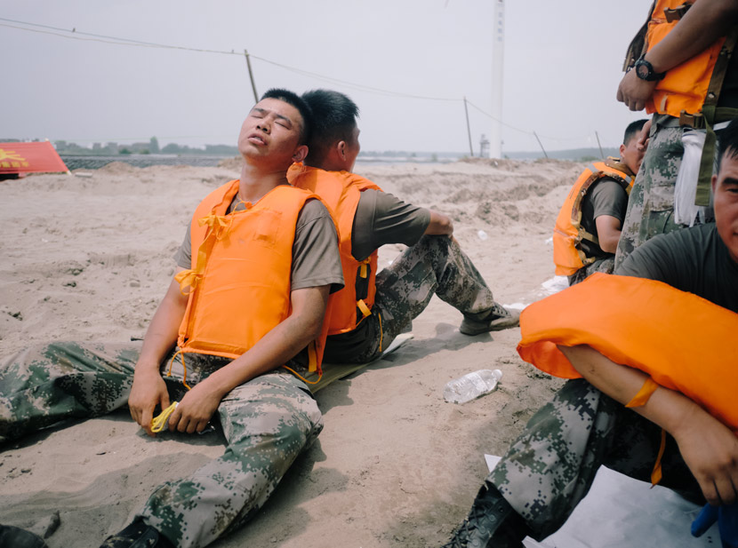 Two soldiers rest back-to-back during their shift reinforcing the dike in Jiangzhou County, Jiangxi province, July 16, 2020. Wu Huiyuan/Sixth Tone