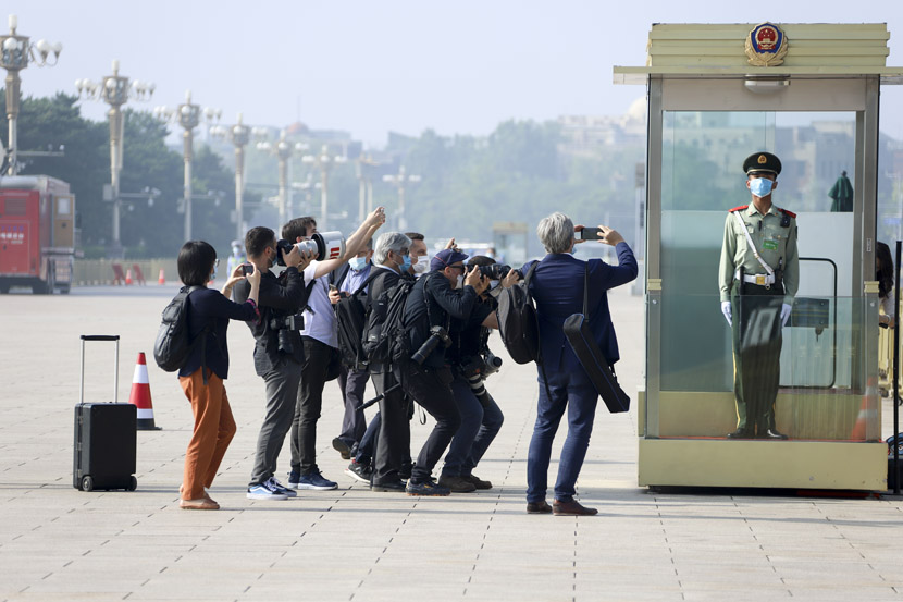 "Journalists snap photos of a guard outside the Great Hall of the People in Beijing, May 22, 2020. This year's ""Two Sessions"" legislative term, delayed by the coronavirus, finally commenced on May 21. People Visual"