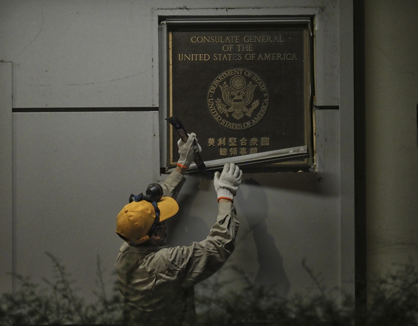 A worker dismantles a sign at the U.S. Consulate in Chengdu, Sichuan province, July 26, 2020. People Visual