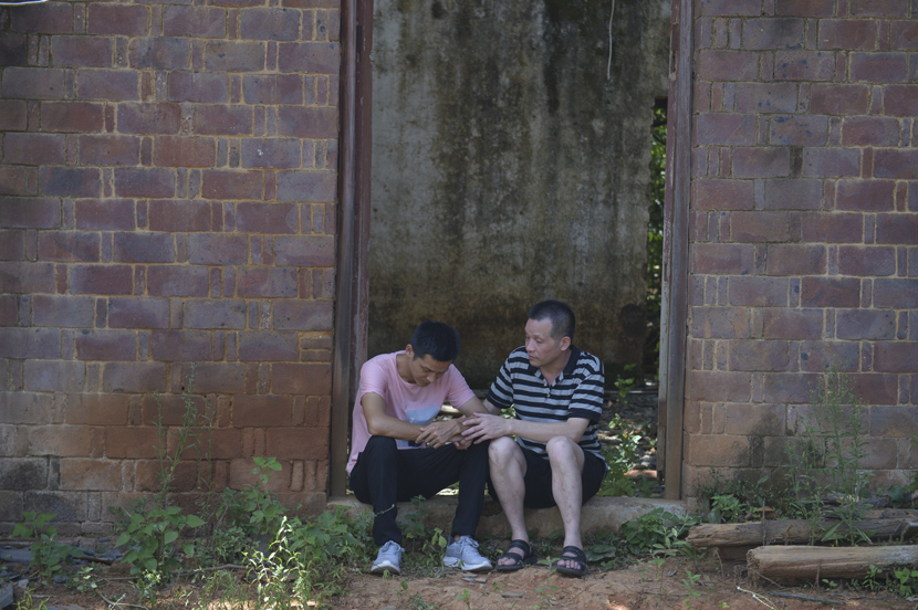 Zhang Yuhuan, who was wrongfully imprisoned for the longest period in China's history, talks to his elder son at their dilapidated house in rural Nanchang, Jiangxi province, Aug. 5, 2020. Wang Qin/Chengdu Business Daily/People Visual