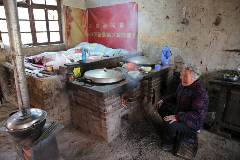 An elderly woman sits by her home's hearth and bed-stoves  in Jiaodai Town, Shaanxi province, April 2019. Wei Yongxian/IC