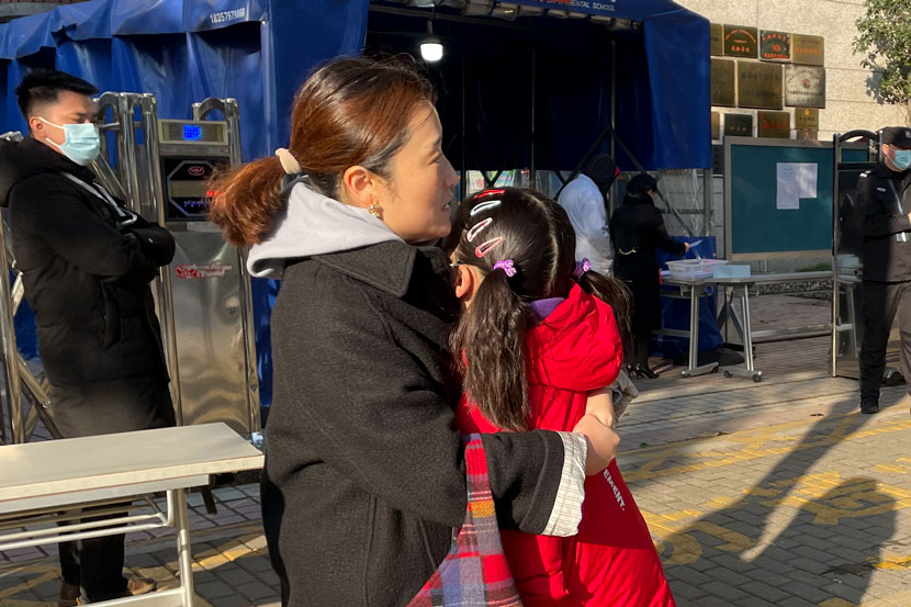 A mother comforts her daughter while waiting for her father to deliver the ID card she needs to get into the test center in Shanghai, Dec. 19, 2020. Zhang Shiyu for Sixth Tone