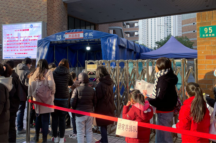 Children line up to get their temperatures tested before entering the test center in Shanghai, Dec. 19, 2020. Zhang Shiyu for Sixth Tone