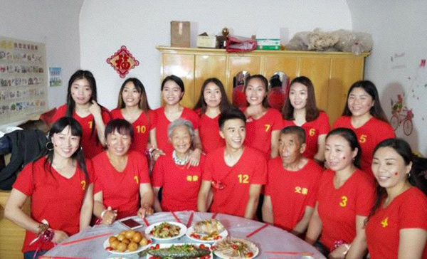 A man poses for a photo with his parents and 11 elder sisters in rural Shanxi province, 2018. Dahe Daily