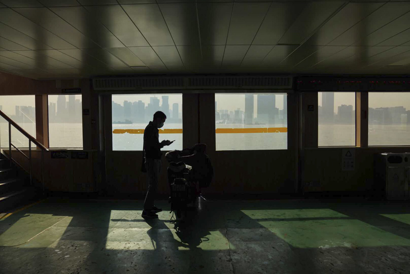 A man rides a ferry on the first day after Wuhan lifted its 76-day lockdown, Wuhan, Hubei province, April 8, 2020. People Visual