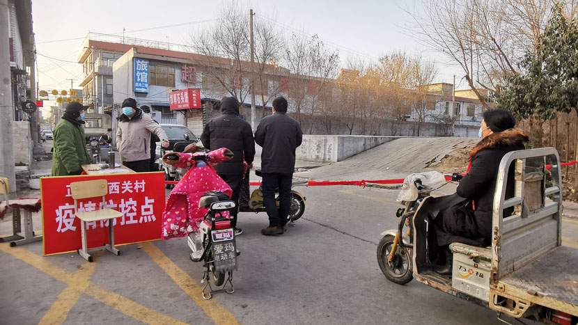 Villagers wait at a checkpoint set up outside Xiguan Village, Shijiazhuang, Hebei province, Jan. 6, 2021. The region has tightened lockdown restrictions after an outbreak of COVID-19 infections. People Visual