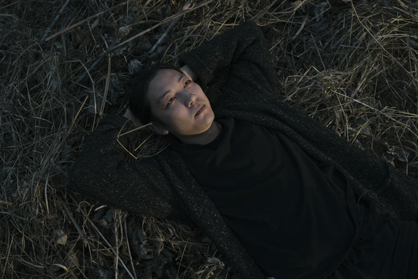 Tang Guanhua, founder of Southern Life Community, rests on a pile of hay, in rural Fuzhou, Fujian province, Dec. 2, 2020. Shi Yangkun/Sixth Tone