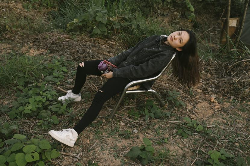 Recent college graduate Fan Yueyi relaxes after spending the day making wine at the commune, in rural Fuzhou, Fujian province, Dec. 2, 2020. Shi Yangkun/Sixth Tone