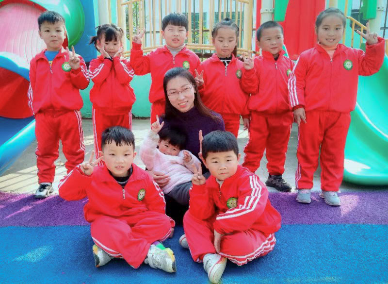 Liu Yue poses for a photo with her daughter and her students at her kindergarten in rural Henan province. Courtesy of Liu Yue