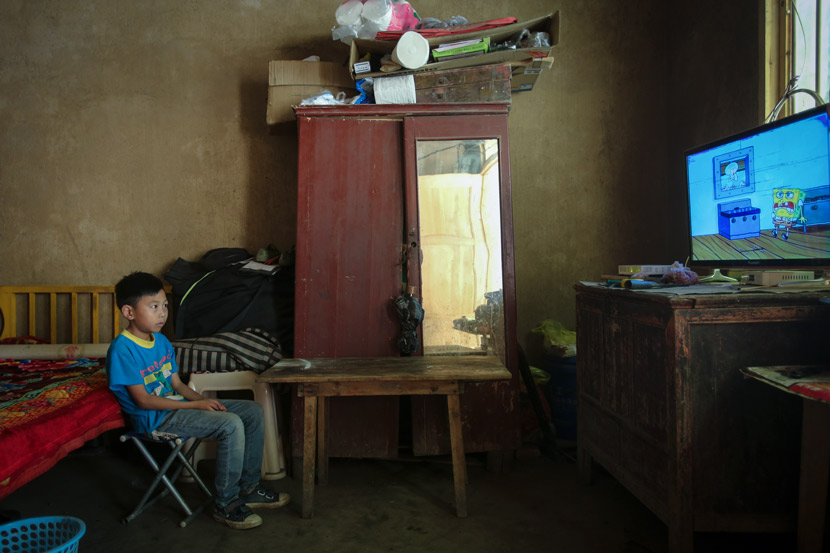 A boy watches TV alone at home, in Bijie, Guizhou province, Aug. 2, 2018. Luo Binhao/People Visual