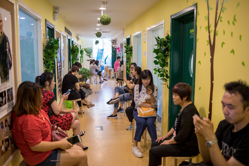Parents wait for their children in a hallway while they attend extracurricular courses in Beijing, 2018. Li Jianguo/People Visual