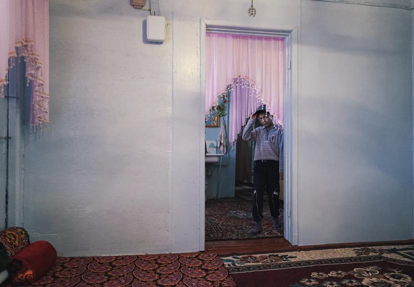 A boy peers through a doorway in his home in northern Uzbekistan, Oct. 9, 2017. Courtesy of Liu Zichao