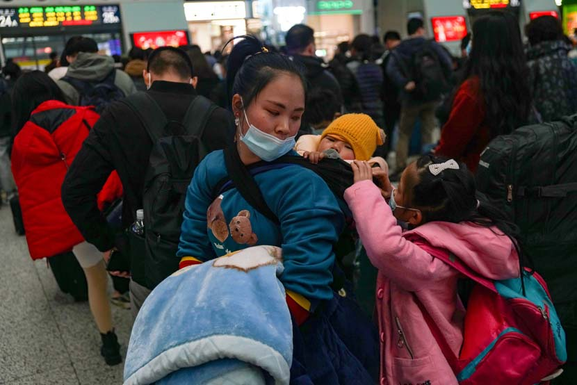 A mother and her children wait in line at a railway station on Thursday, the beginning of this year's Spring Festival travel period, in Hangzhou, Zhejiang province, Jan. 28, 2021. IC