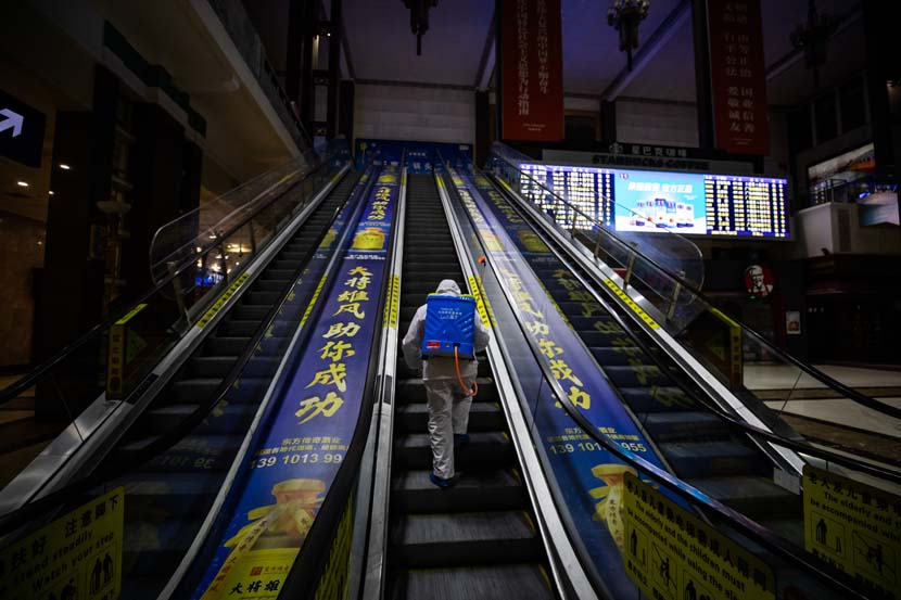 A disease control worker sterilizes an escalator at Beijing Railway Station, Jan. 27, 2021. People Visual