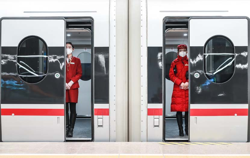 Attendants wait for passengers to board a train at Beijing Railway Station, Jan. 28, 2021. People Visual