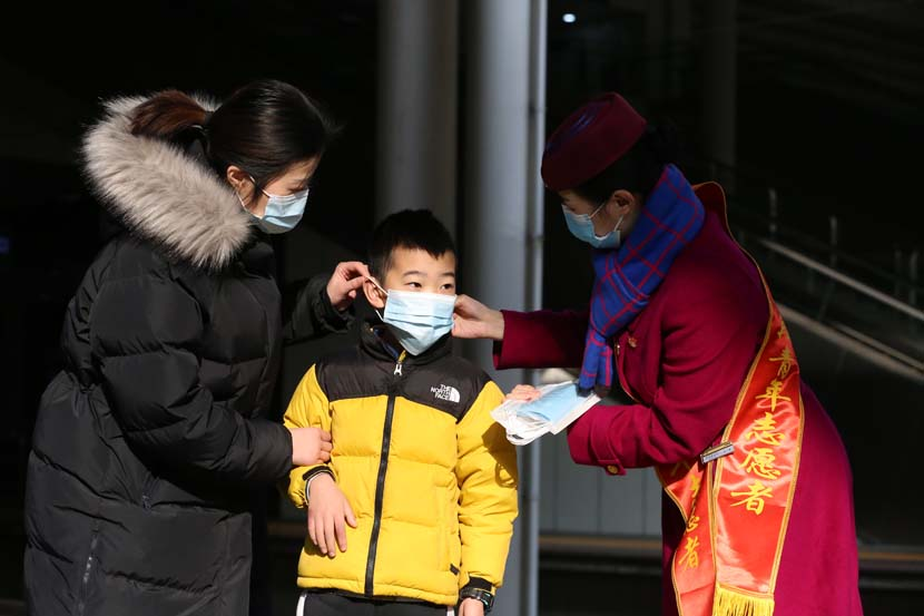 A volunteer helps a boy wear his mask properly at Chongqing North Railway Station, Jan. 28, 2021. People Visual