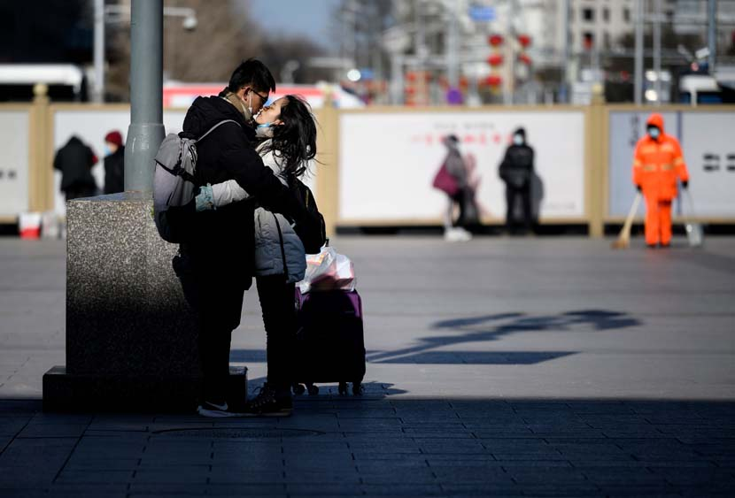 A couple parts with a kiss on the first day of the Spring Festival travel period outside Beijing Railway Station, Jan. 28, 2021. People Visual