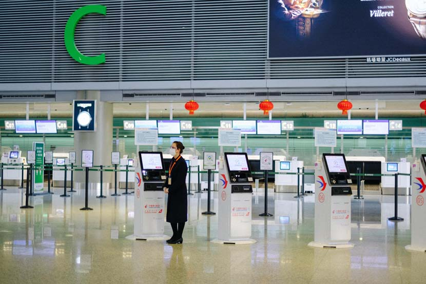 A China Eastern Airlines staff member waits to assist checking-in passengers at Shanghai Hongqiao International Airport, Jan. 28, 2021. Wu Huiyuan/Sixth Tone