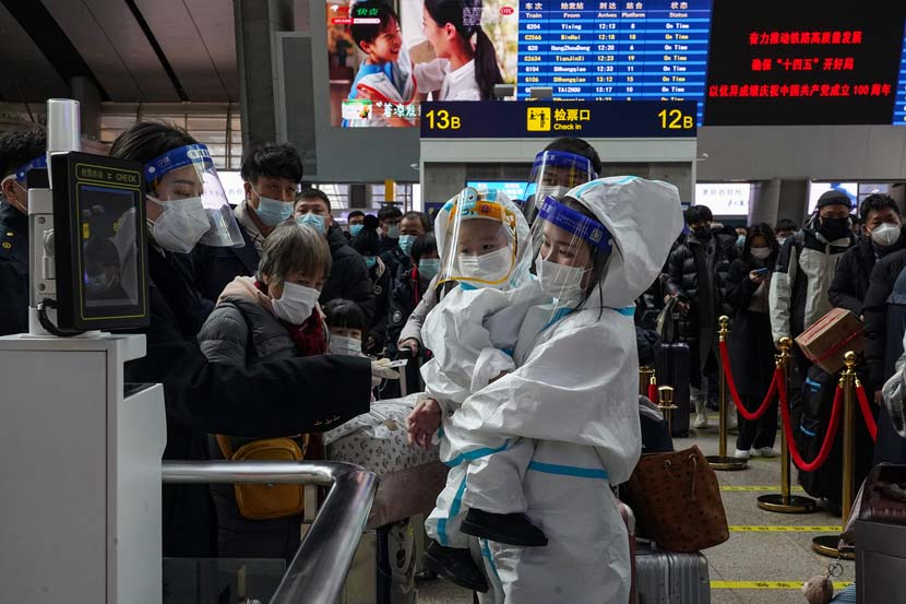 A mother and child in full hazmat suits pass through an automatic ticketing gate at Beijing South Railway Station, Jan. 28, 2021. Wang Jiaxing/China Youth Daily