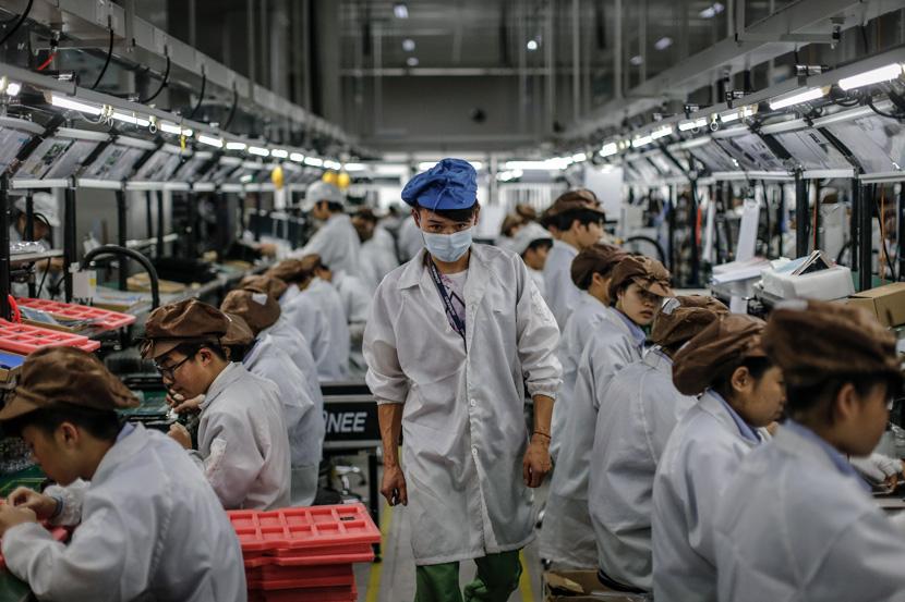A worker walks through a workshop in Dongguan, Guangdong province, 2015. Liu Xingzhe/People Visual