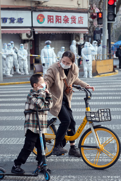 A mother and son walk past a blocked-off neighborhood in Shanghai, Jan. 27, 2021. Lü Wei/People Visual