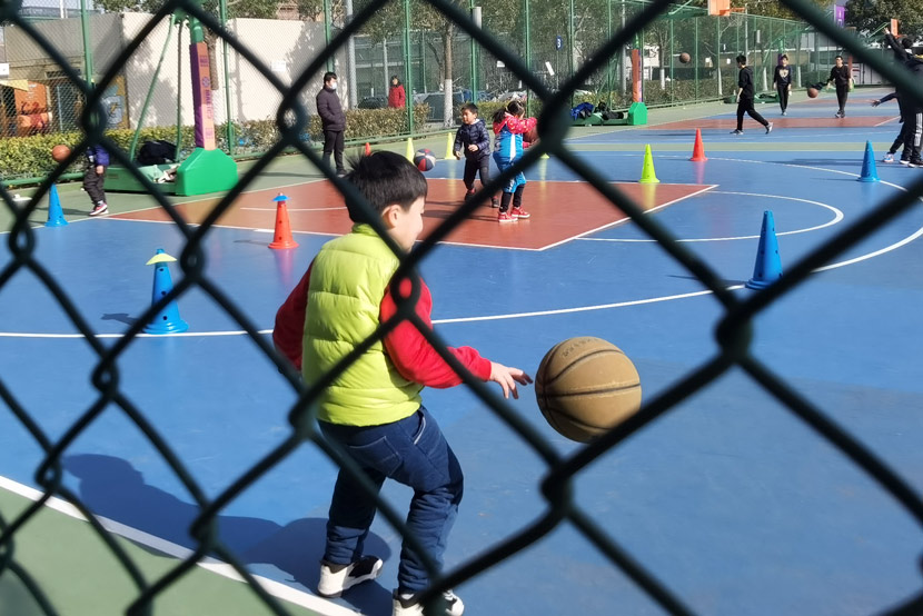 Children take part in a basketball training session run by a private training company in Shanghai, Jan. 9, 2021. Ni Dandan/Sixth Tone