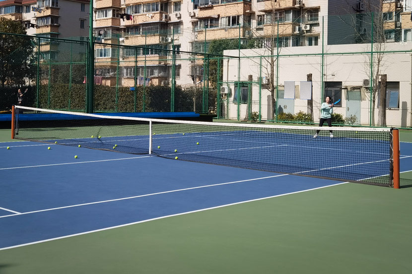 A student practices tennis with a private coach at a court in Pudong New Area, Shanghai, Jan. 9, 2021. Ni Dandan/Sixth Tone