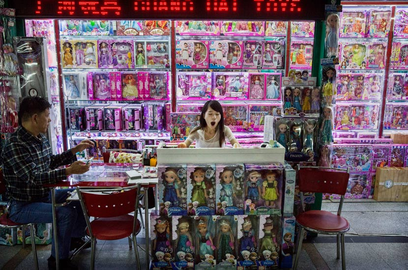 A trader yawns as she waits for customers to visit her stall at the Yiwu International Trade City mall, Zhejiang province, 2015. Kevin Frayer/Getty Images/People Visual