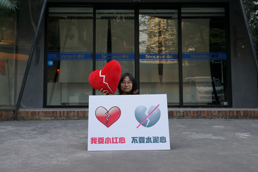 An artist holding a poster showing old (left) and new emojis poses for a photo in front of WeChat's headquarters in Guangzhou, Guangdong province, Jan. 30, 2021. Courtesy of Wang Huadong