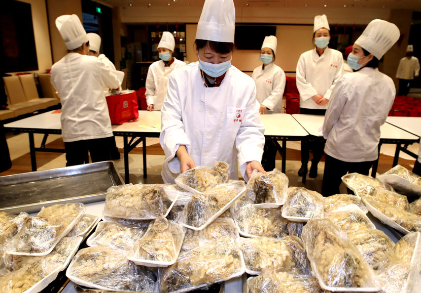 Kitchen staff prepare dishes for a Spring Festival meal at a restaurant in Suzhou, Jiangsu province, Feb. 9, 2021. Wang Jianzhong/People Visual